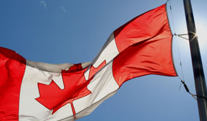 Canadian flag blowing in the wind, lit from behind