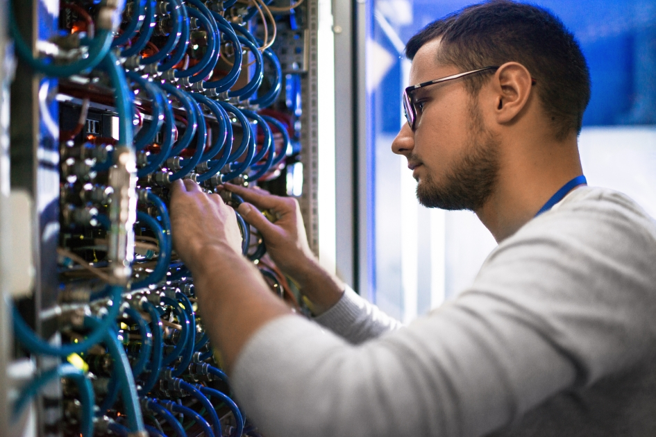 An information technology worker rewiring computer server.