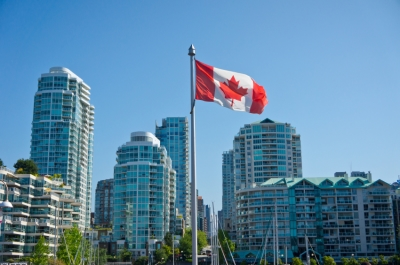 The Canadian flag fluttering in the city.