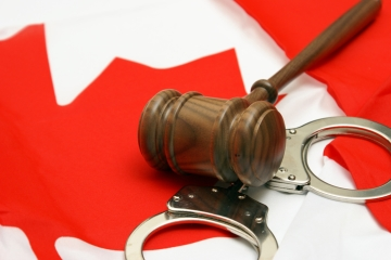 A gavel and set of handcuffs resting on a Canadian flag