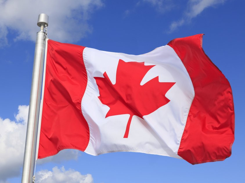 Canada flag with mountain view on the background.