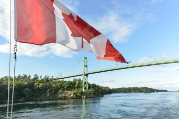 A Canadian flag waving on the St. Lawrence River in front of the Thousand Islands Bridge, connecting Ontario, Canada and New York State in the United States