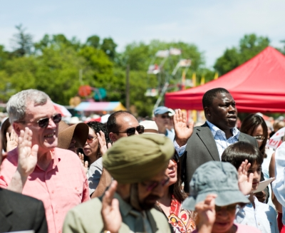New citizens to Canada take the oath of citizenship at a citizenship ceremony