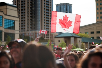Canadian flag waved over a crowd in a busy urban setting