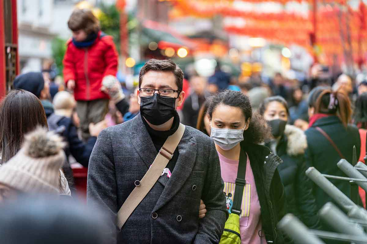 Man and woman wearing face-masks on a busy street during coronavirus pandemic.