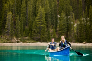 Two young people kayaking on a lake in Canada
