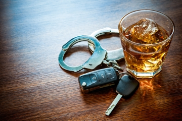 A set of car keys, hancuffs, and a glass of liquor on a table