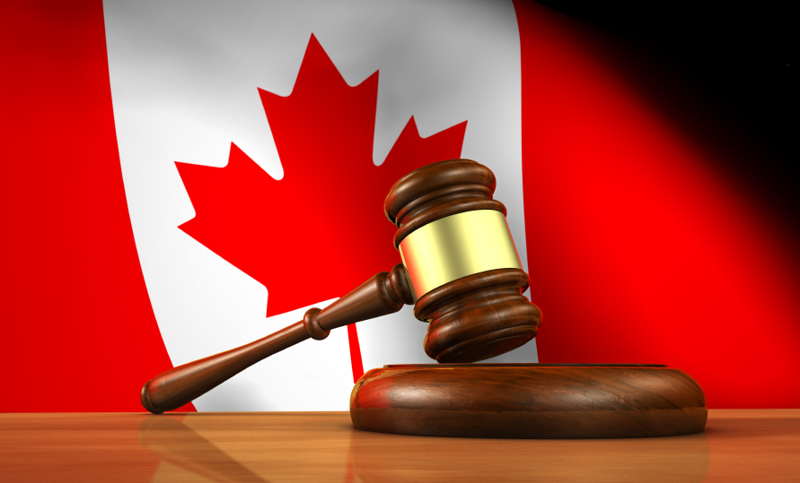 A gavel resting in front of a Canadian flag