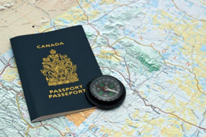 A Canadian passport and compass resting on a map of Canada