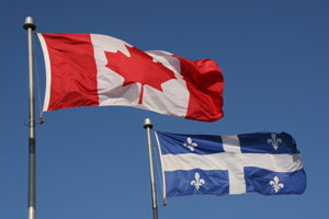 Quebec and Canadian flags blowing in front of a blue sky