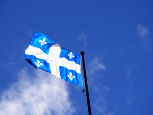 The flag of Quebec waving against a blue sky
