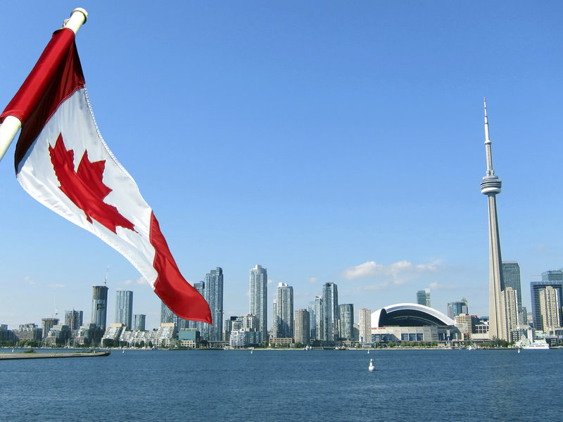 A Canadian flag flutters, with the Toronto skyline in the background