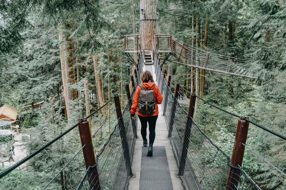 A girl with a backpack crossing Capilano Bridge in Vancouver, British Columbia.
